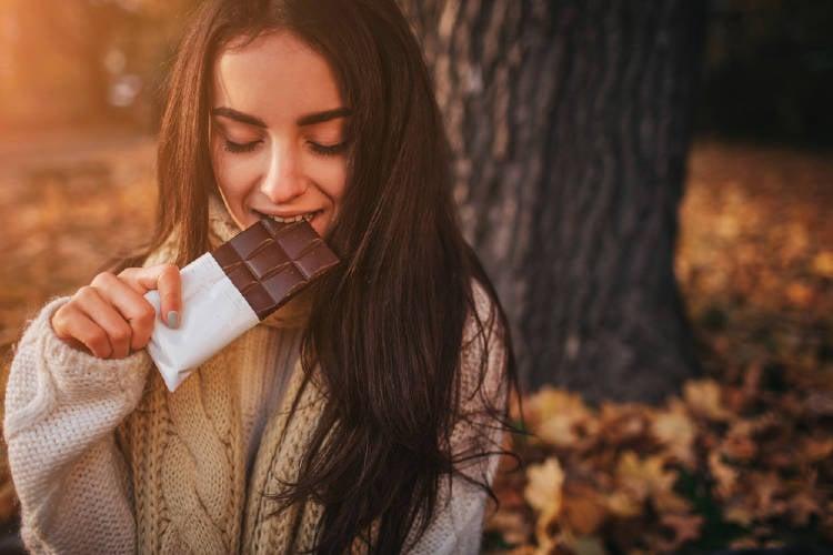 Una mujer comiendo una barra de chocolate