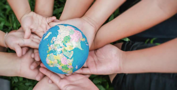 manos de pequeños sostienen la representacion del planeta tierra buscando construir un mundo mejor