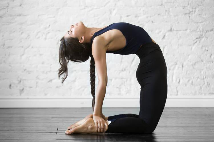 Una mujer en la postura de yoga de la cuerda del arco