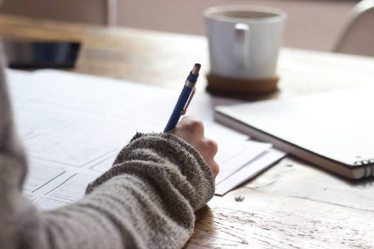Una persona escribiendo en un escritorio con una taza de café