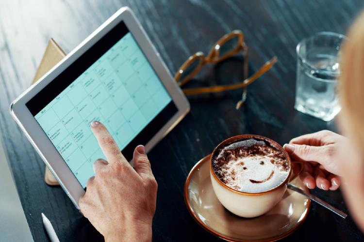 Una persona toma café mientras revisa su agenda