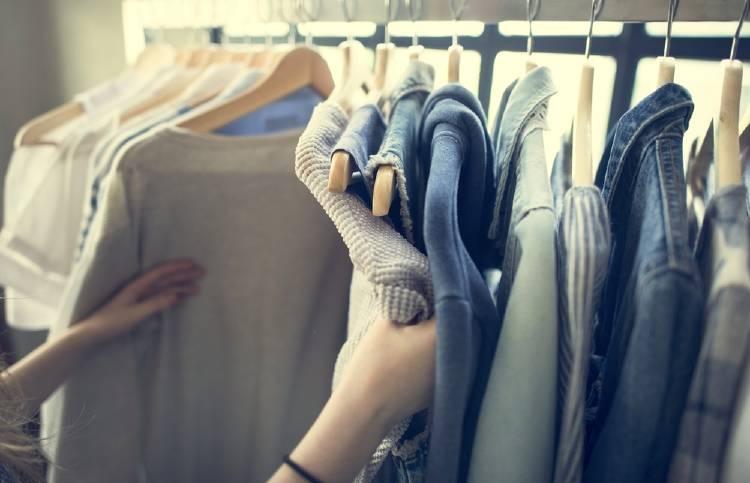 perchero con prendas de ropa, camisas y camperas, en los tonos azules