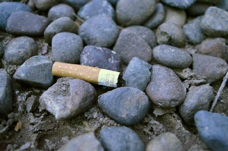 Una colilla de cigarrillo tirada en un suelo de piedras