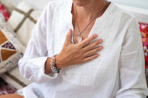 mujer lleva su mano hacia su pecho, el centro de energia emocional