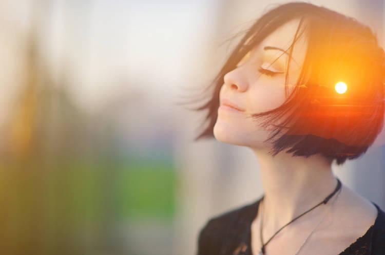 mujer morocha piensa positivamente y su glándula pineal se ilumina en el centro de su cabeza