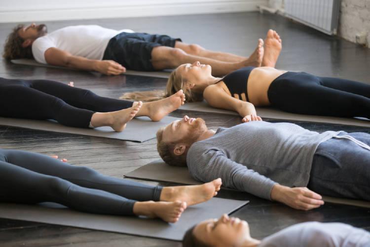 yoguis practican yoga nidra en una clase
