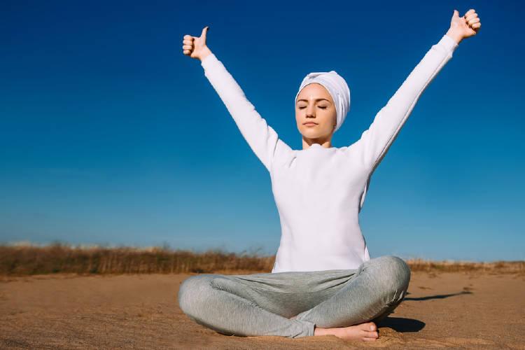 mujer yogui realiza un ejercicio de respiración al aire libre