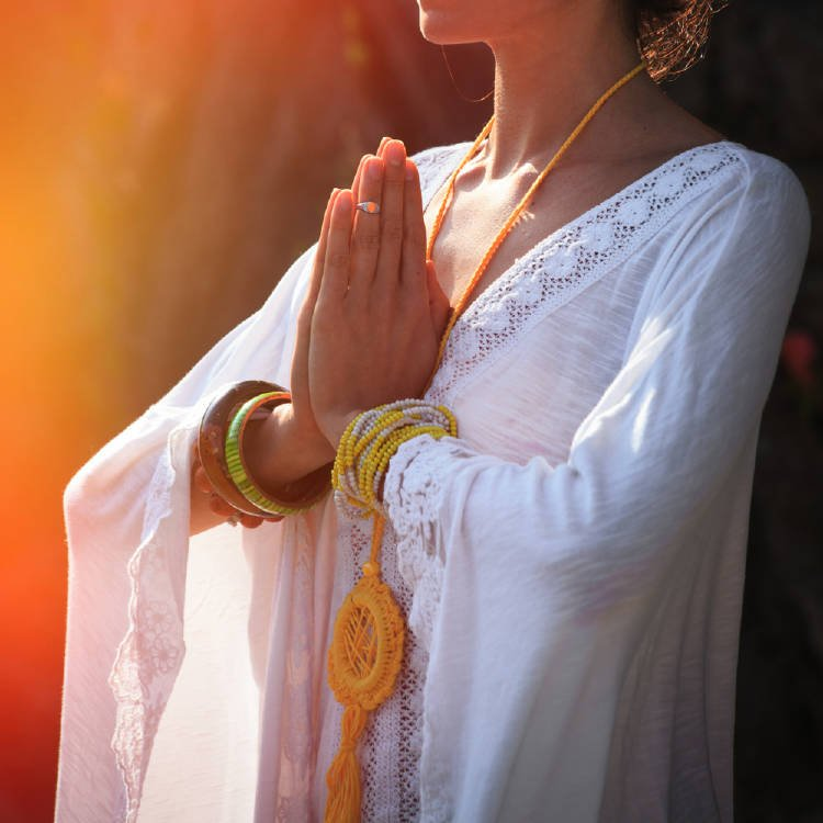 Mujer de vestido blanco uniendo sus manos en el centro de su pecho.
