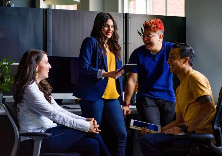 Un grupo de personas conversa divertida en una oficina