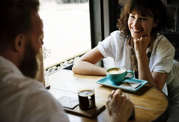 Un hombre y una mujer conversan  y toman café en un bar