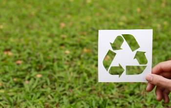 Símbolo del reciclaje sobre pasto