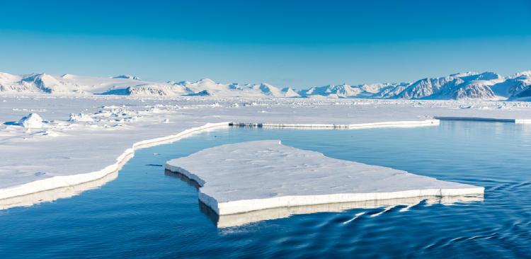 Trozo gigante de hielo flotando en el mar azul al lado de un glaciar