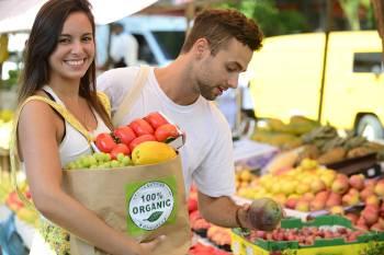 Dos jóvenes compran orgánico en una feria