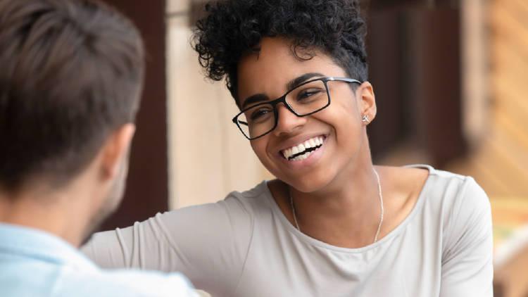 mujer negra con lentes sonrie
