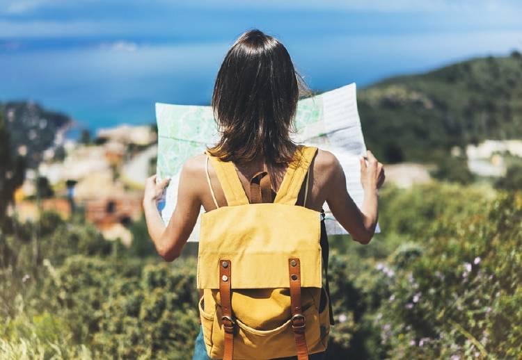 mujer joven viajando sosteniendo mapa