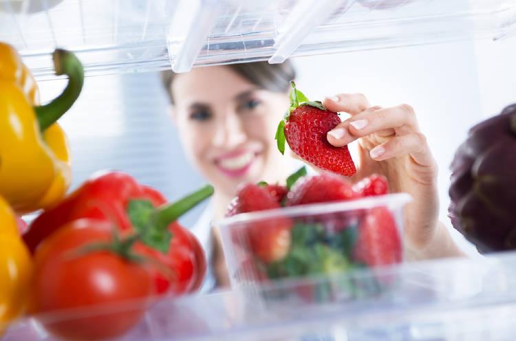 Una mujer toma fresas de la nevera