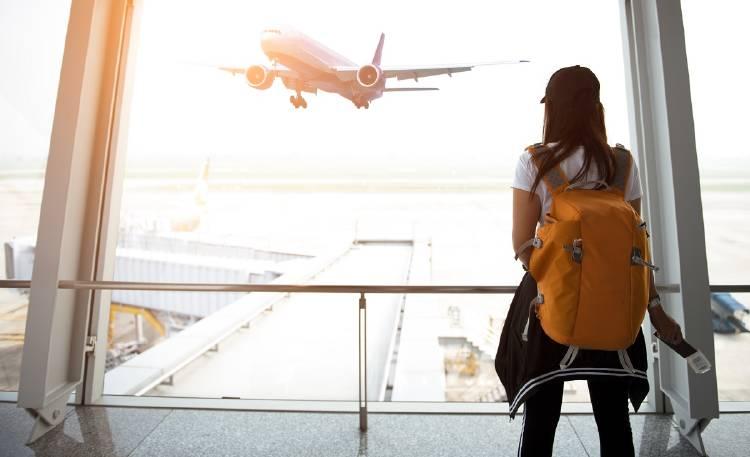 Una joven mira un avión que despega en un aeropuerto