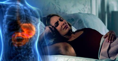 mujer en la cama con dolor de estomago