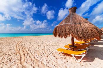 playa del carmen limpia con palapas en primer plano