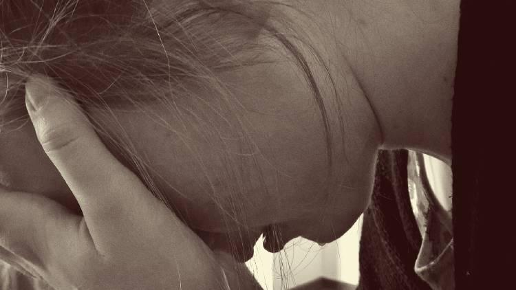 Una mujer llorando se cubre el rostro con las manos