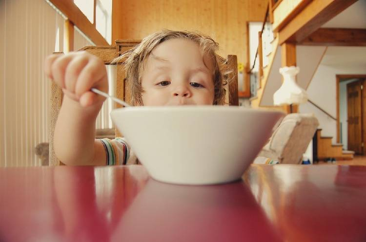 Un niño comiendo de un recipiente