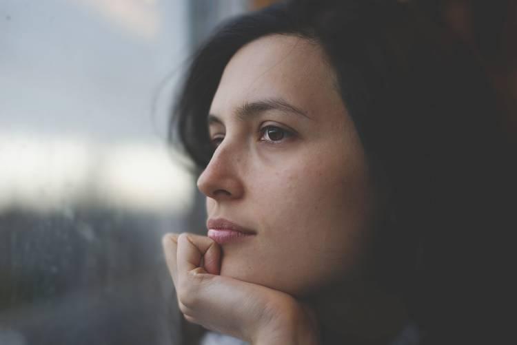 Una mujer mira por la ventana pensativa