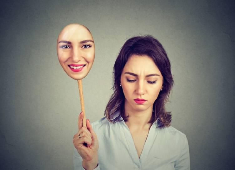 Una mujer se quita la máscara y revela un rostro triste
