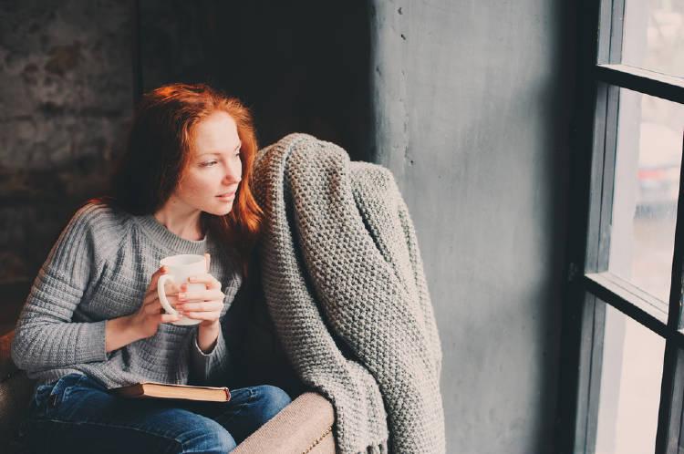 mujer pelirroja disfruta de un libro y un cafe en su hogar hygge