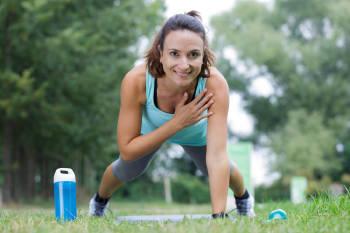 Una mujer haciendo el ejercicio de la plancha en un parque