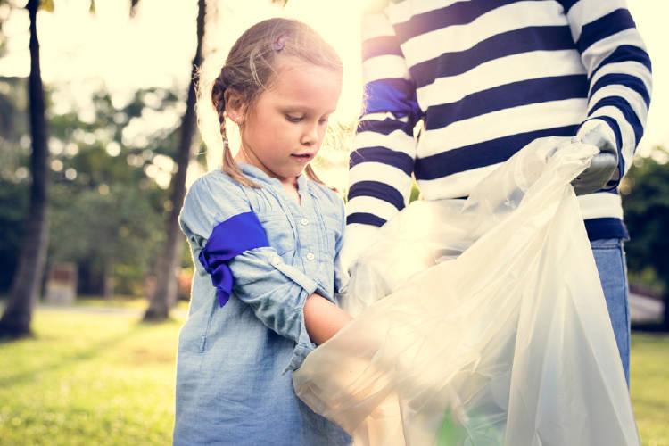 Una niña arrojando residuos en una bolsa en un parque