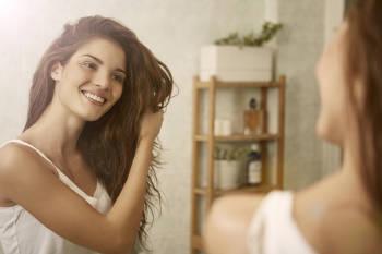 Mujer acomoda su cabello con gel de lino frente al espejo