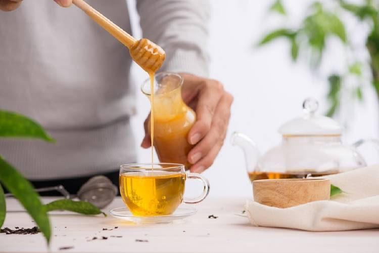 Un hombre endulza un té con miel