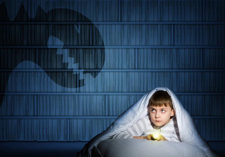 Un niño con miedo imagina que una sombra es un dinosaurio