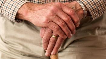 Manos de un abuelo con un anillo de matrimonio apoyadas en un bastón