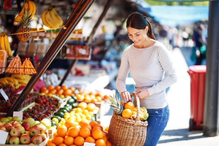 mujer compra frutas y verduras en un mercado local