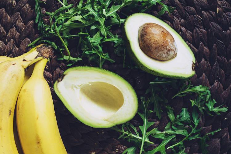 Media aguacate y dos plátanos sobre una mesa