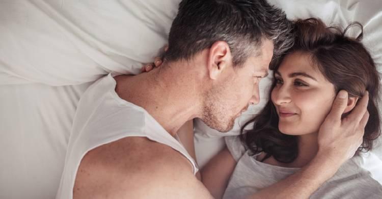 Una pareja se mira en la cama