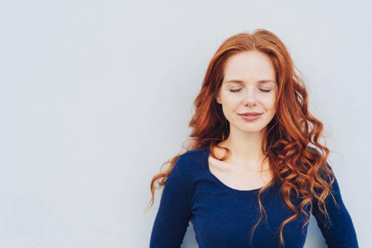 Una mujer pelirroja con los ojos cerrados