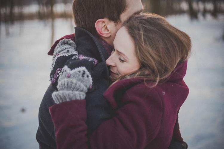 Una pareja se abraza en un lugar frío