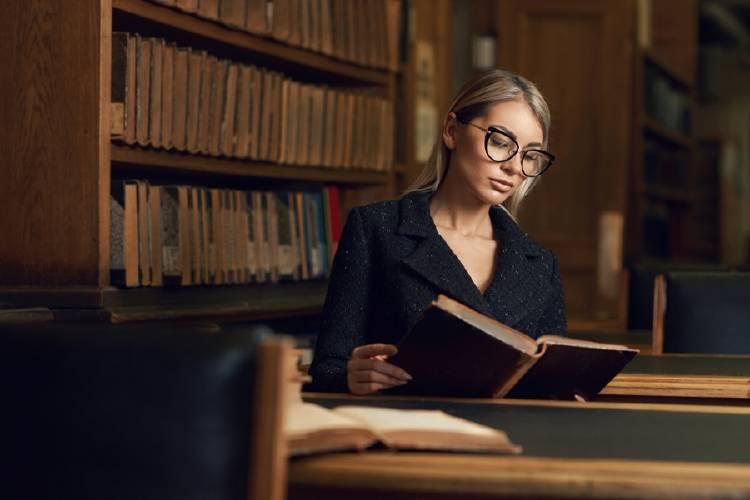 mujer con lentes leyendo en la biblioteca