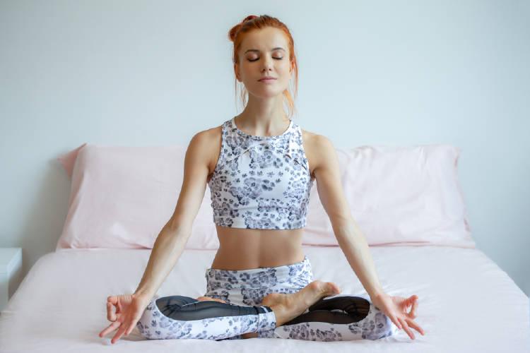 joven practica meditacion en la cama