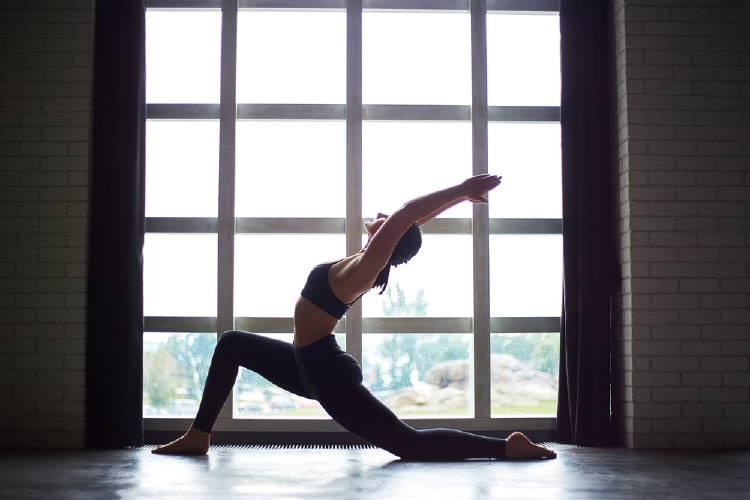 Una mujer haciendo yoga frente a un ventanal