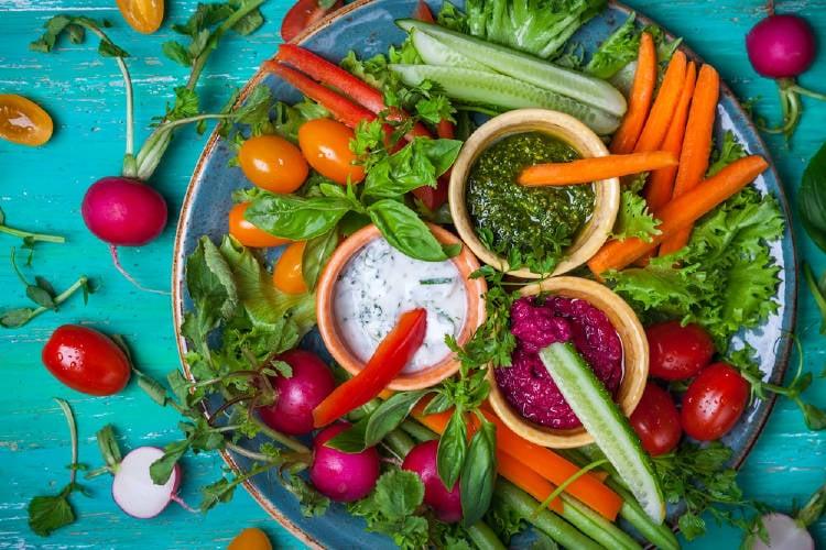 Dips con vegetales alrededor