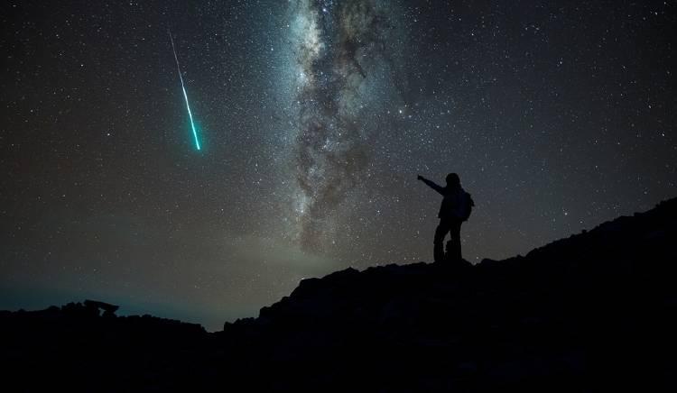 hombre observando estrella fugaz
