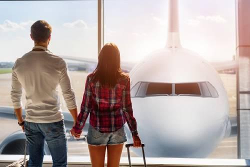 pareja tomada de la mano frente a avion en aeropuerto