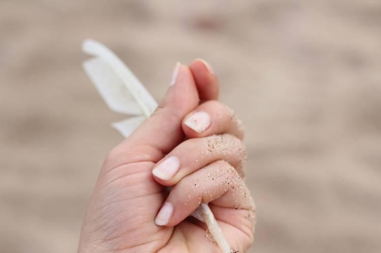 Una mujer sostiene una pluma sobre un fondo de arena