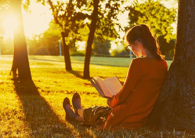 mujer lee apoyada en un arbol