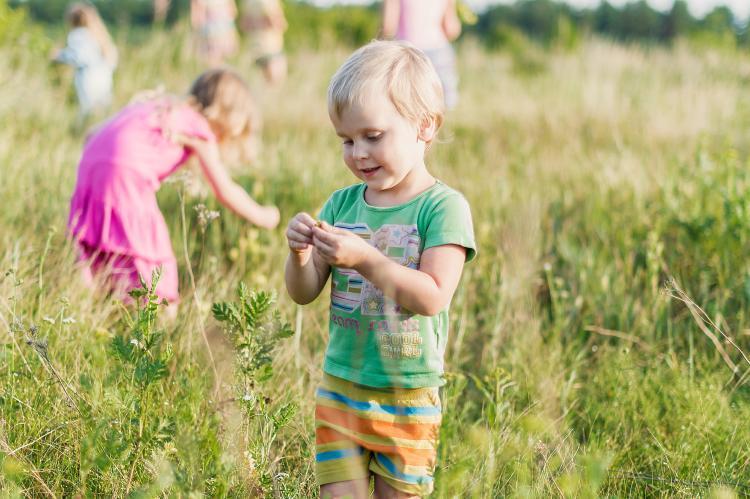 Niño jugando en un pastizal