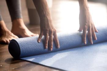 Esterilla de yoga sostenida por dos manos