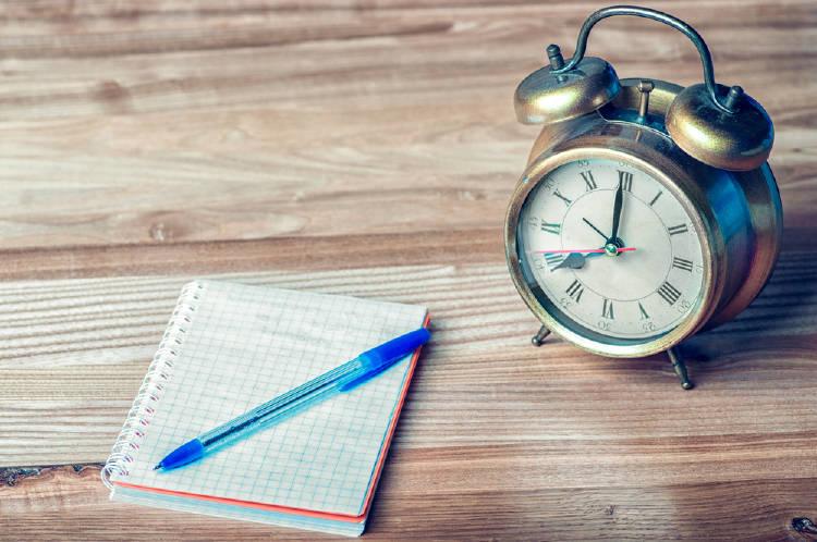 Un cuaderno al lado de un reloj despertador